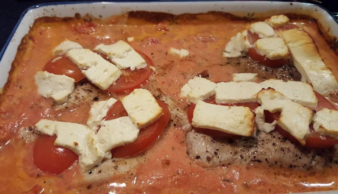 Putenschnitzel mit Tomatenscheiben und Schafskäse belegen